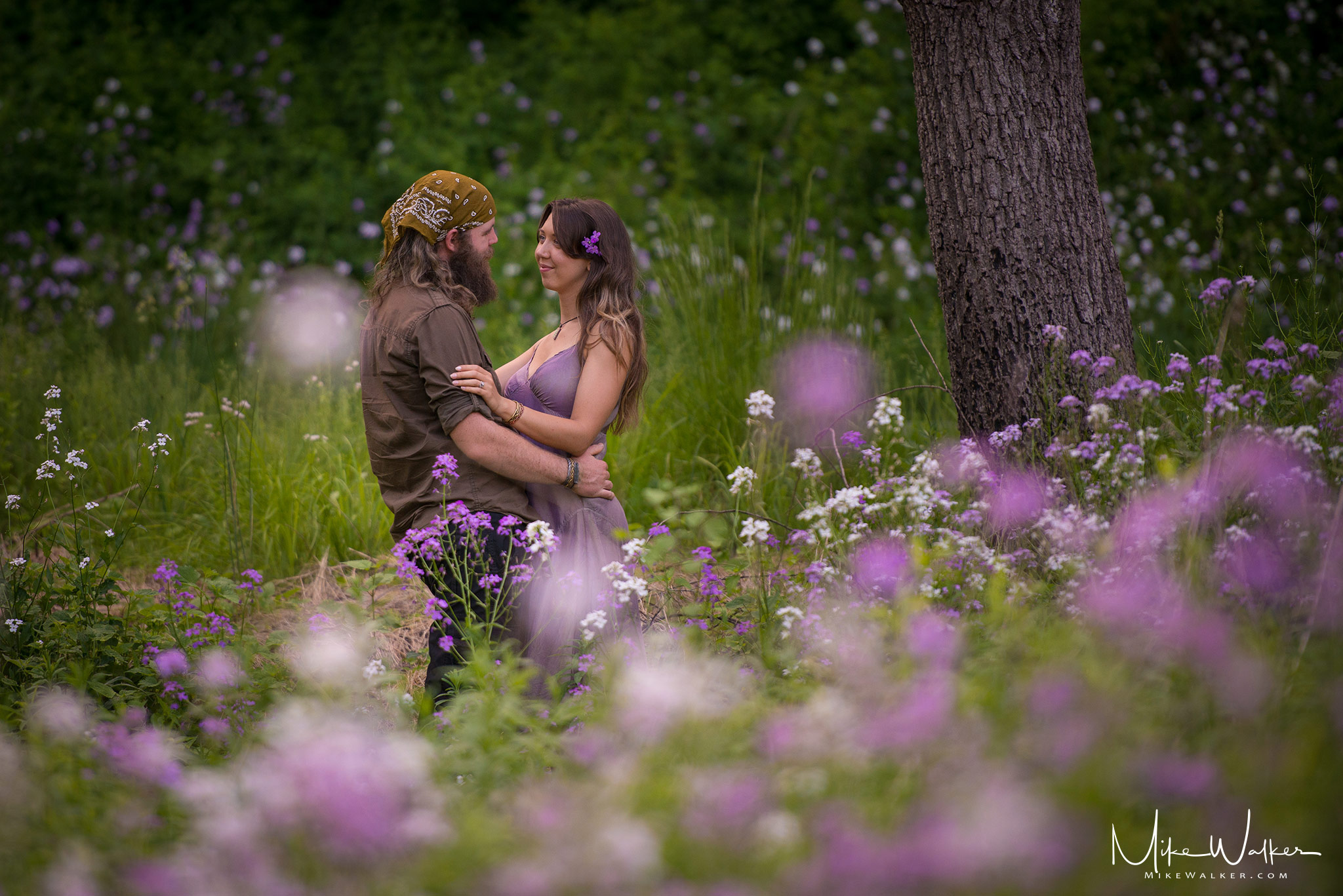 Engaged couple in field of wildflowers. Engagement photography by Mike Walker.