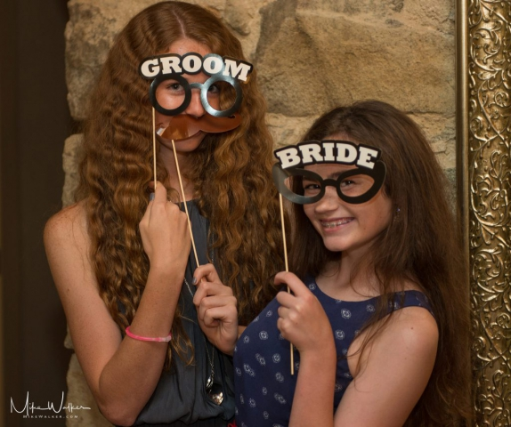 Girls at a sweet 16 party with photo booth props. Event photographer Mike Walker.