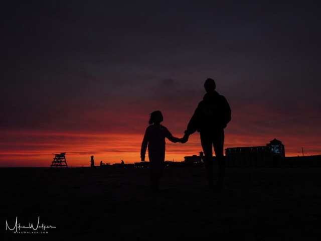 Silhouette of sisters holding hands on the beach. Family photography by Mike Walker.
