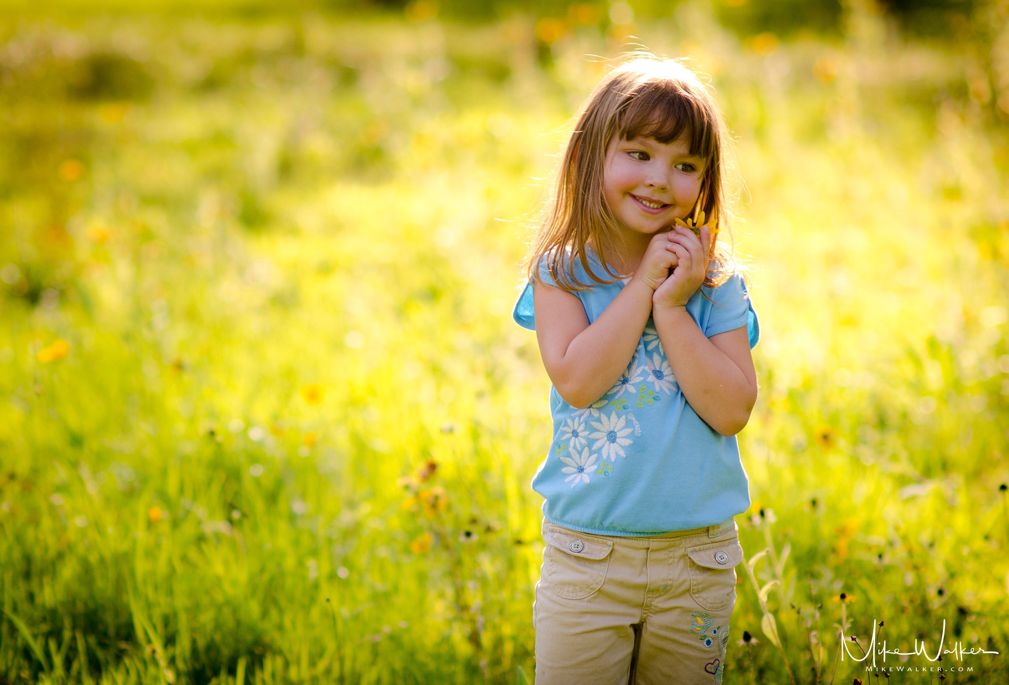 Young girl in a field of wildflowers. Family photographer Mike Walker.