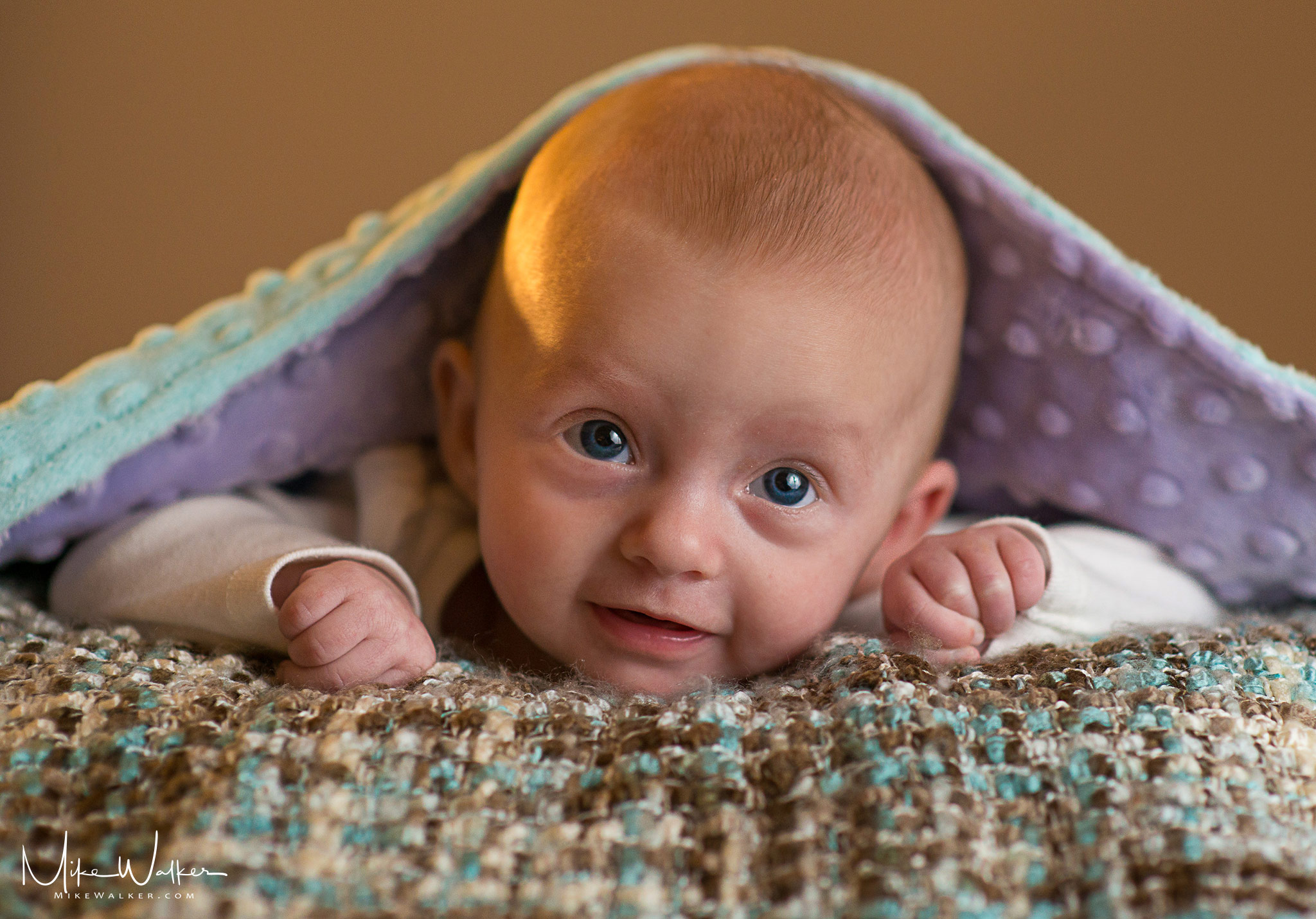 A baby peaking out of a blanket. Family photographer Mike Walker.