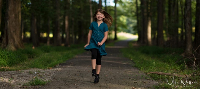 A girl skipping down a path in the woods. Family Photography by Mike Walker.