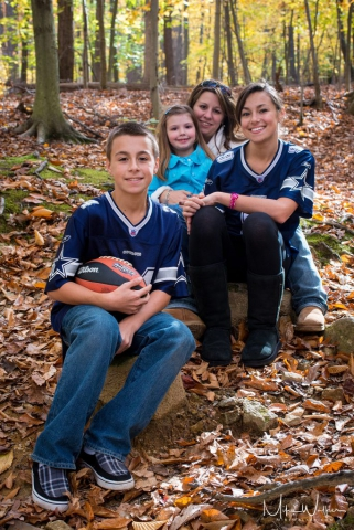 Family in the woods in the fall. Family photographer Mike Walker.
