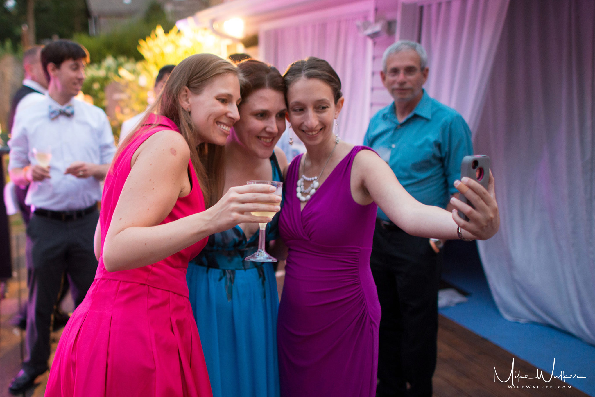 Group of women taking a selfie at a wedding. Wedding photography by Mike Walker.