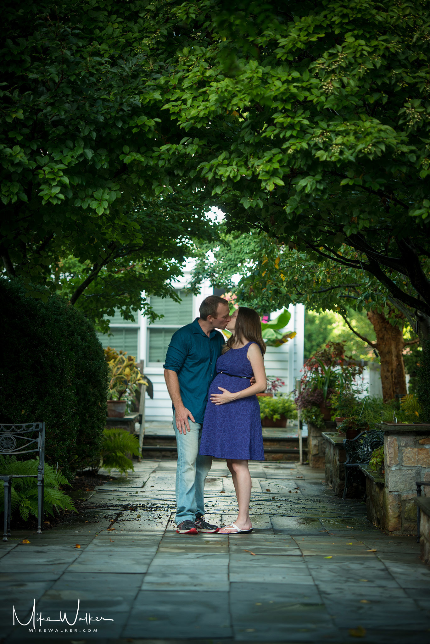 Pregnant couple in a garden. Maternity photography by Mike Walker.