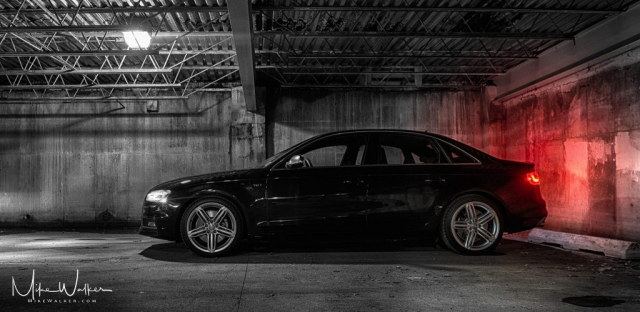 Mostly black and white image of an Audi S4 in a grungy parking garage. Automotive photography by Mike Walker.