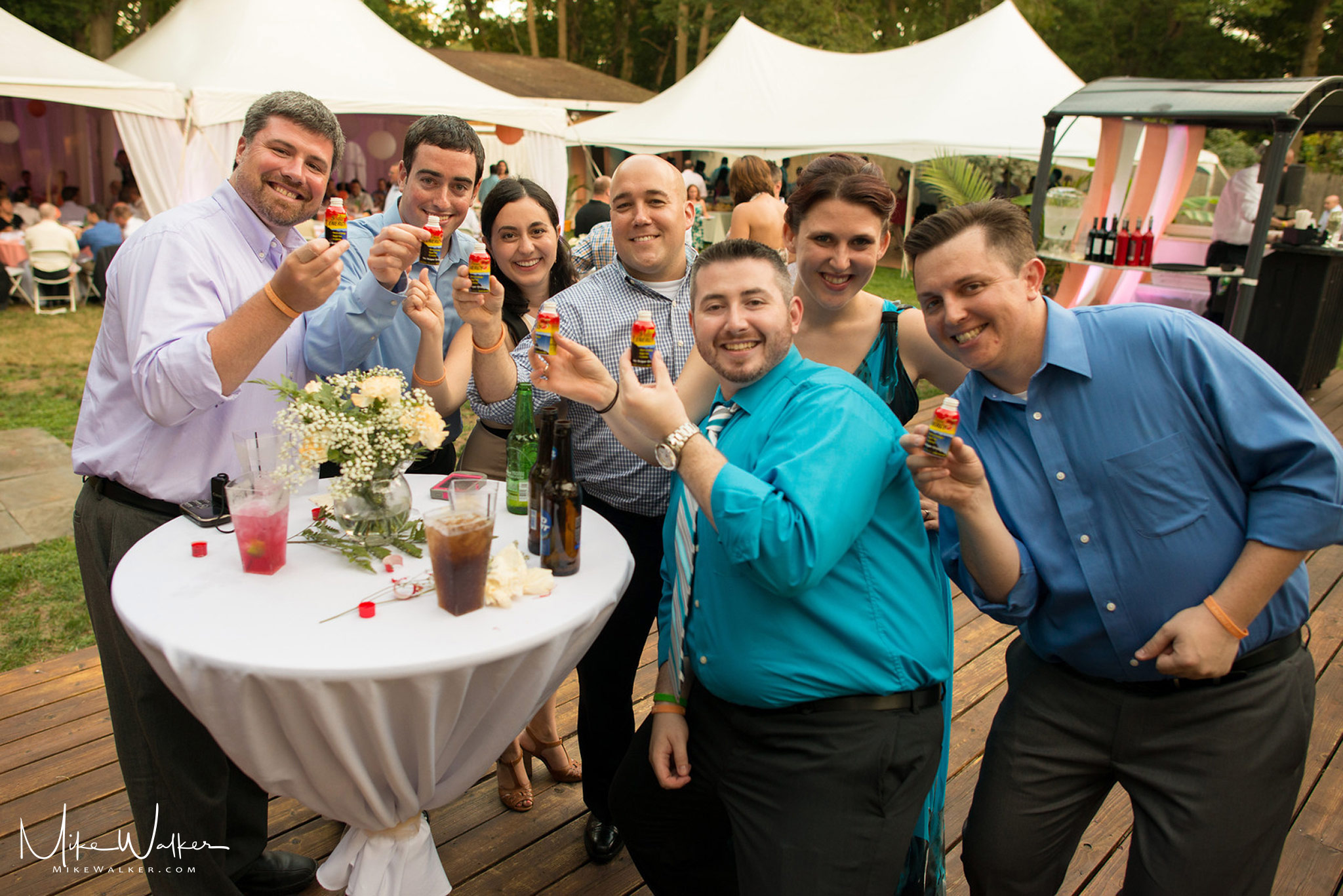 Group at a wedding doing 5-hour energy shots. Wedding photographer Mike Walker.