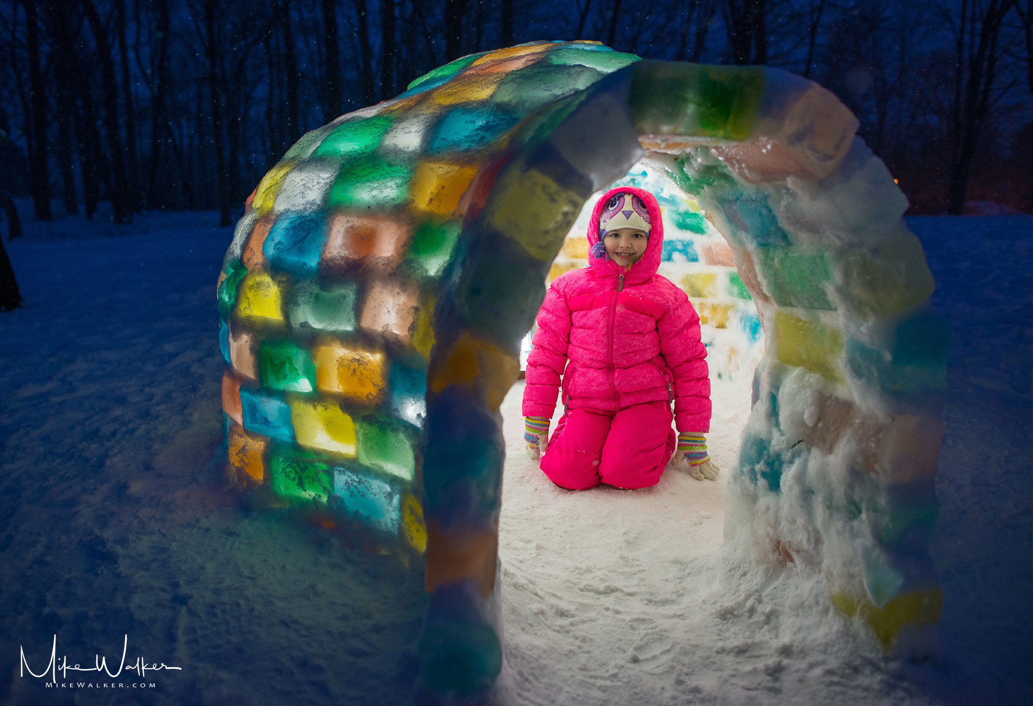 Girl inside an igloo made with colored ice blocks. Family photography by Mike Walker.