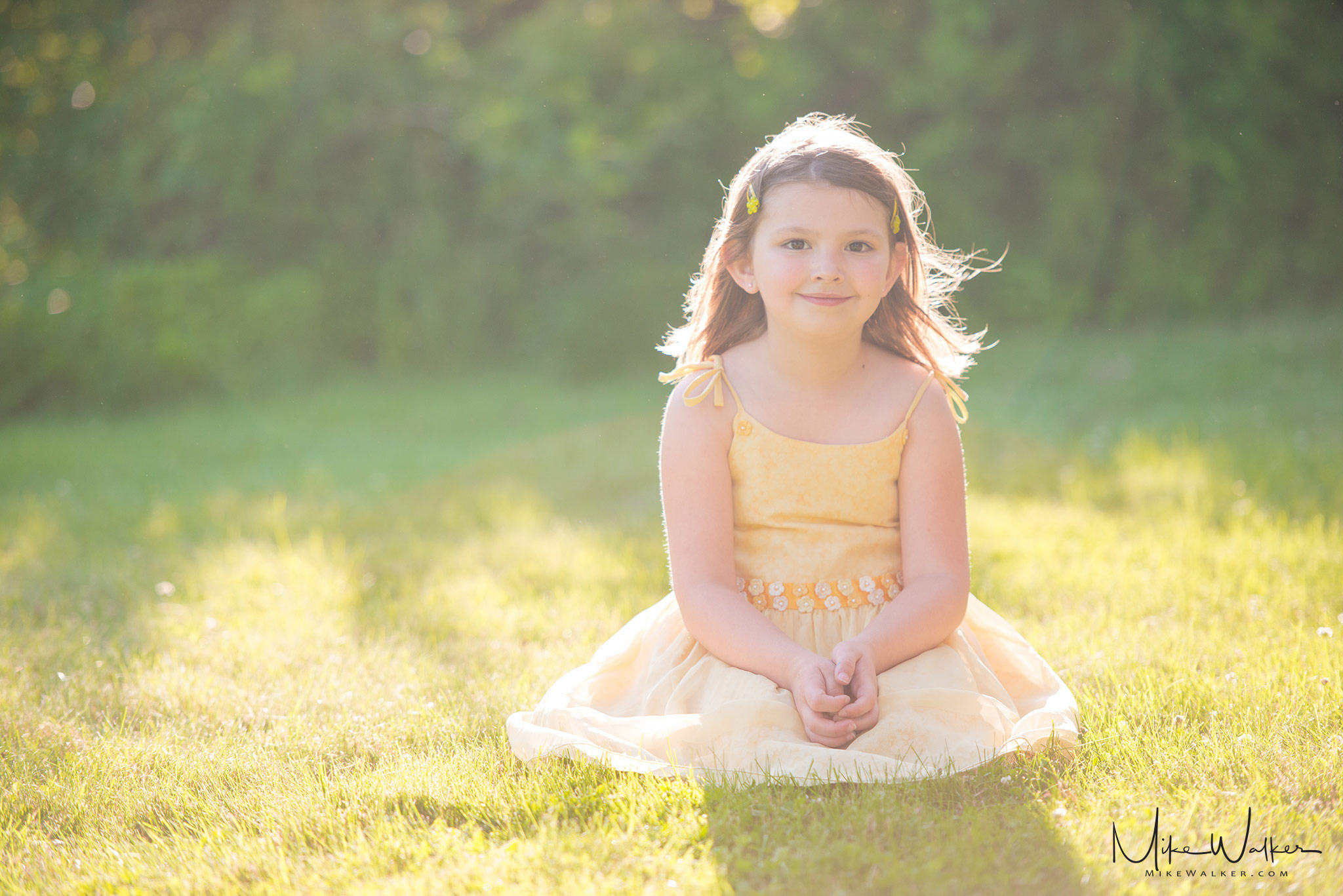 Young girl sitting in the grass in a sunny backyard. Family photography by Mike Walker.
