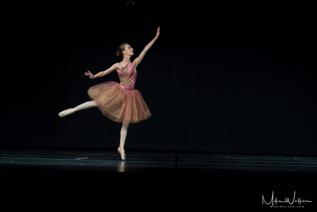 Young girl performing ballet on stage. Family photography by Mike Walker.