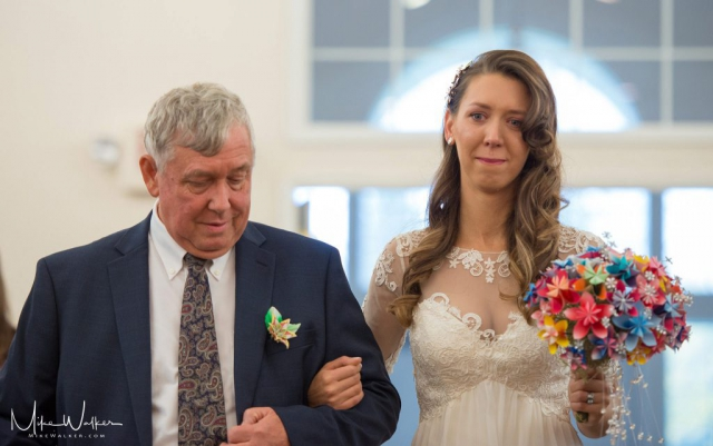Father walking his daughter down the isle at her wedding. Wedding photography by Mike Walker.