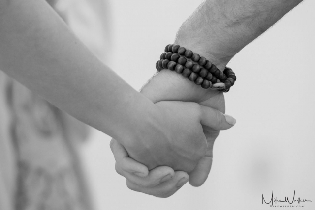 Couple holding hands during wedding ceremony. Wedding photography by Mike Walker.