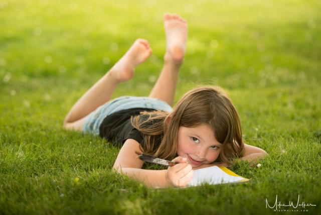 Young girl writing songs in the grass. Family photography by Mike Walker.