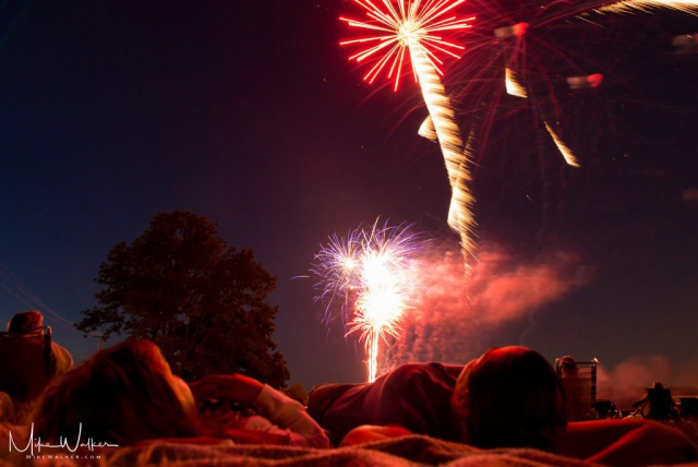 Low perspective of people laying on the ground enjoying fireworks. Family photography by Mike Walker.