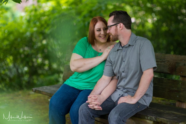 Engaged couple sitting on a park bench. Wedding photography by Mike Walker.