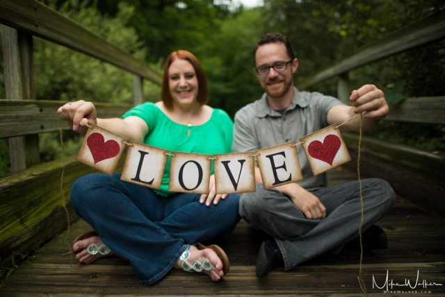 Engaged couple holding a sign that says LOVE. Engagement session by Mike Walker.
