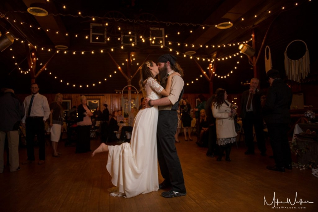 Bride and groom kissing in the middle of the dance floor at their reception. Wedding photography by Mike Walker.