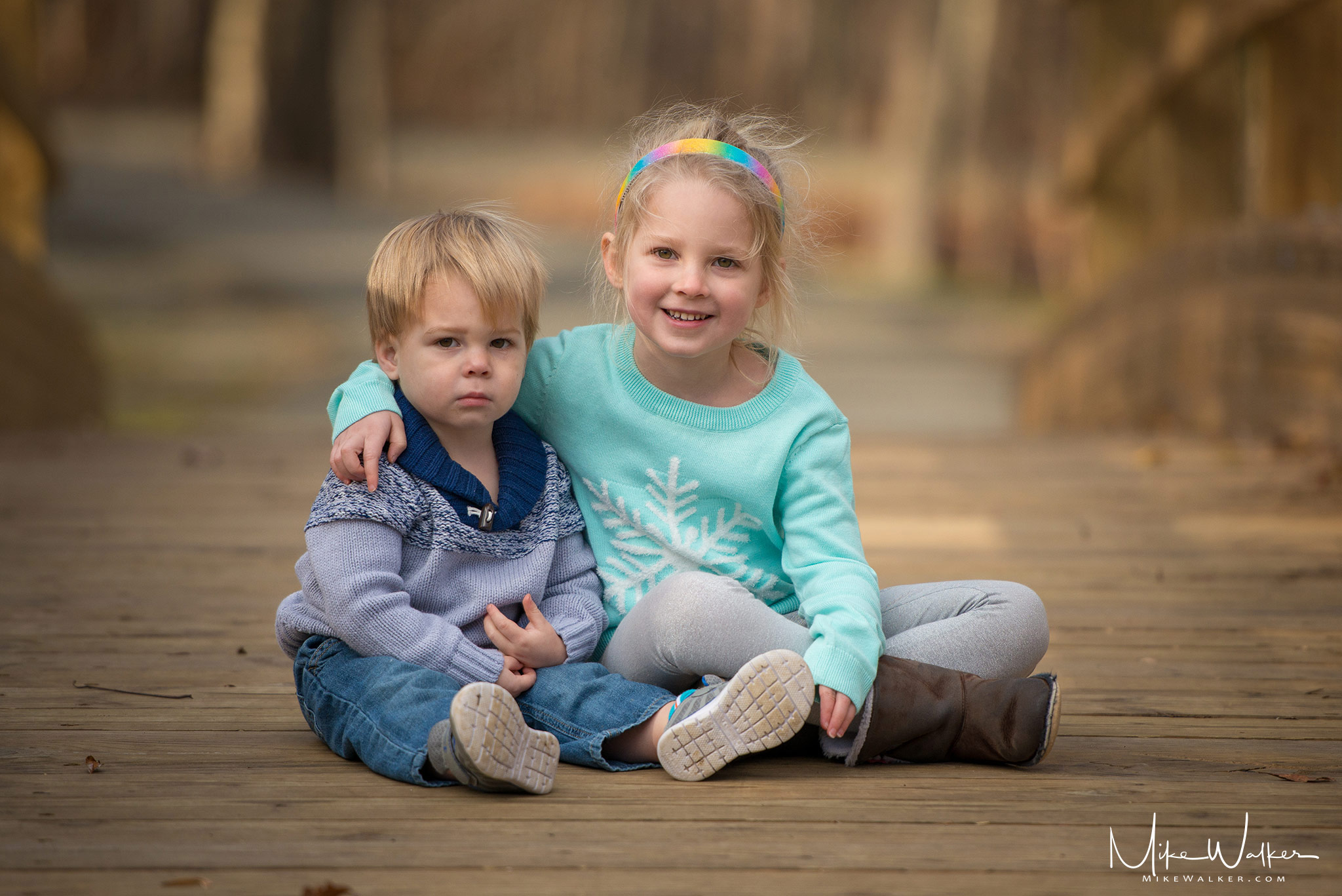 Two children posing. One is smiling. Family photography by Mike Walker.