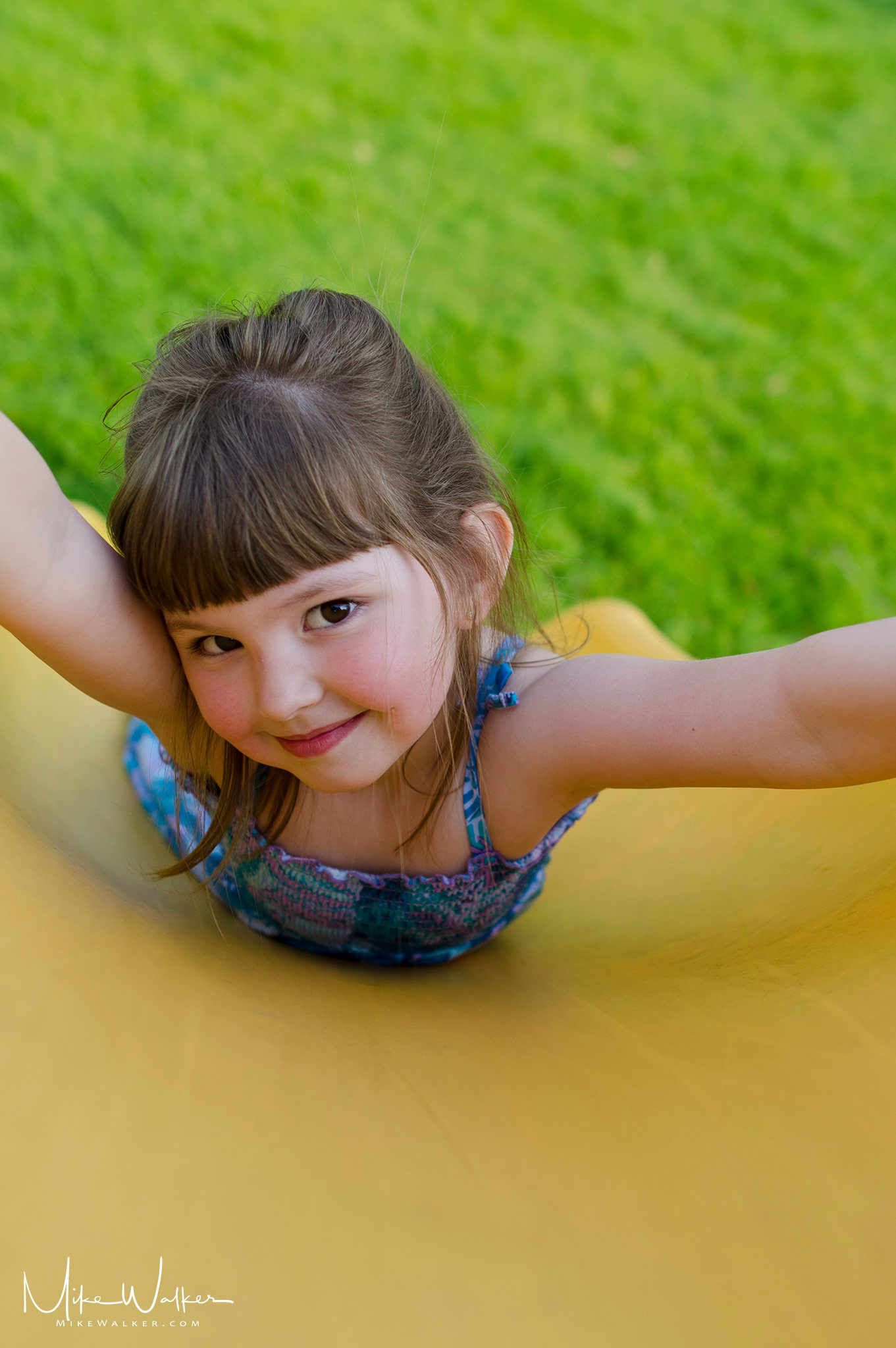 Young girl sliding down a slide. Family photography by Mike Walker.