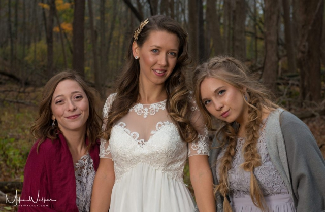 Bride and bridesmaids posing in the woods. Wedding photography by Mike Walker.