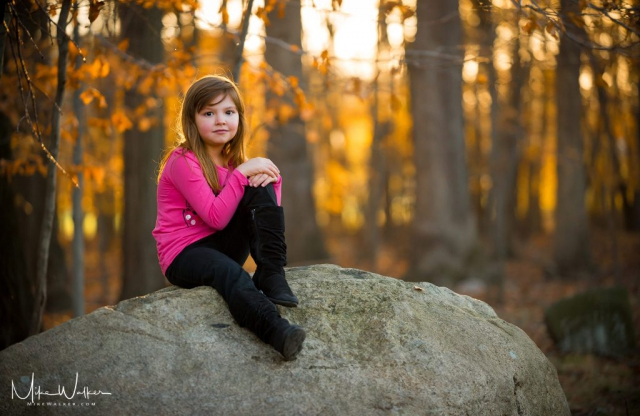 Young girl sitting on a rock. Family photography by Mike Walker.