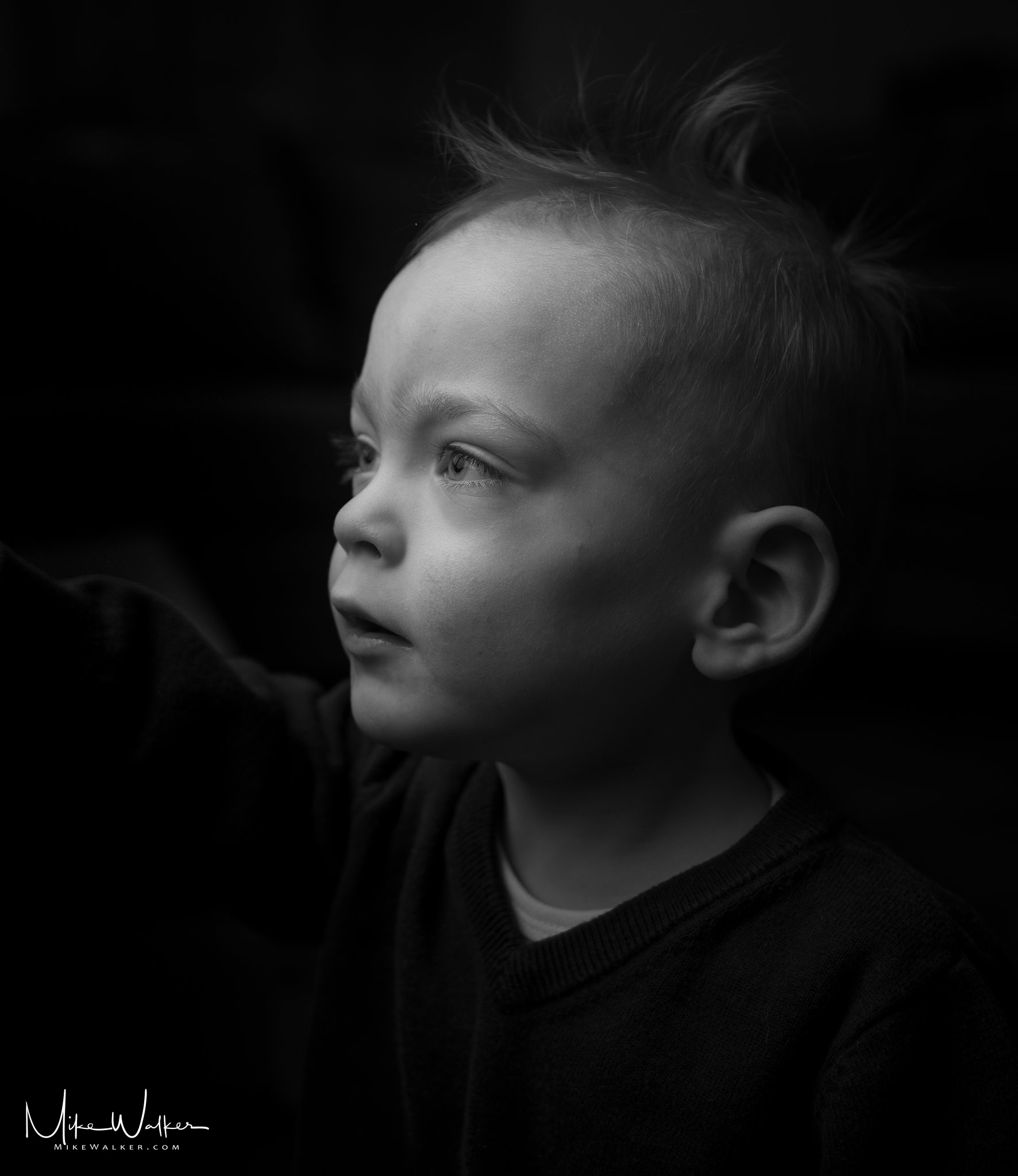 Young boy checking out some lighting. Family photography by Mike Walker.