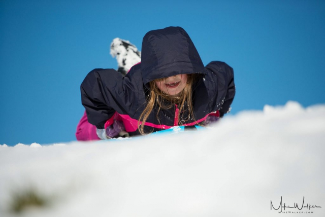 Young girl sledding down a hill with a bright blue sky in the background. Family photography by Mike Walker.
