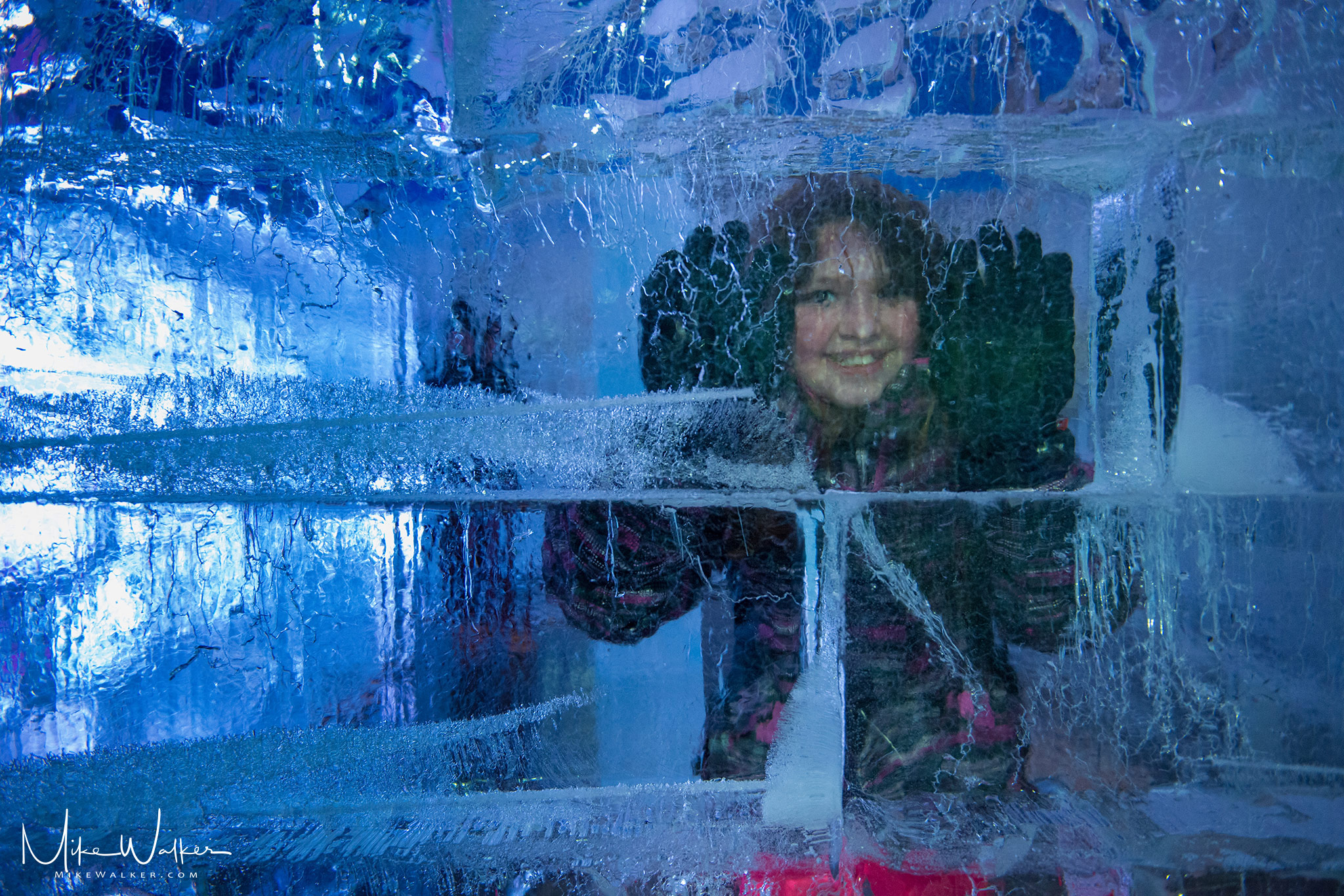Young girl behind a wall of ice. Family photography by Mike Walker.