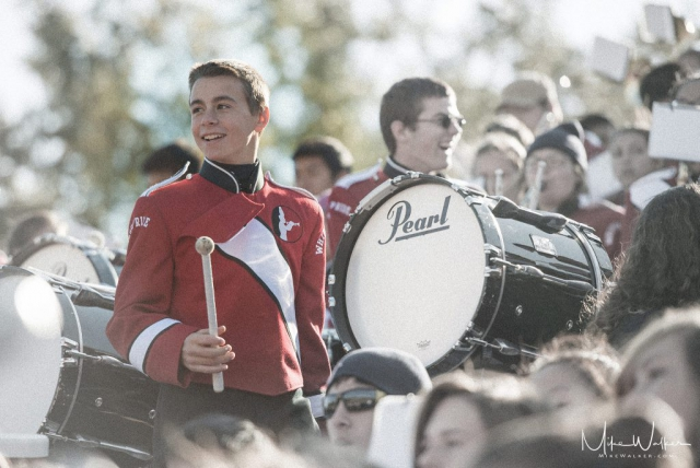 Young man in a marching band with a bass drum. Family photography by Mike Walker.